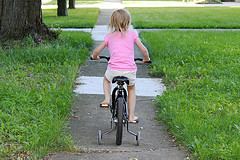 Little girl riding a bike with training wheels.